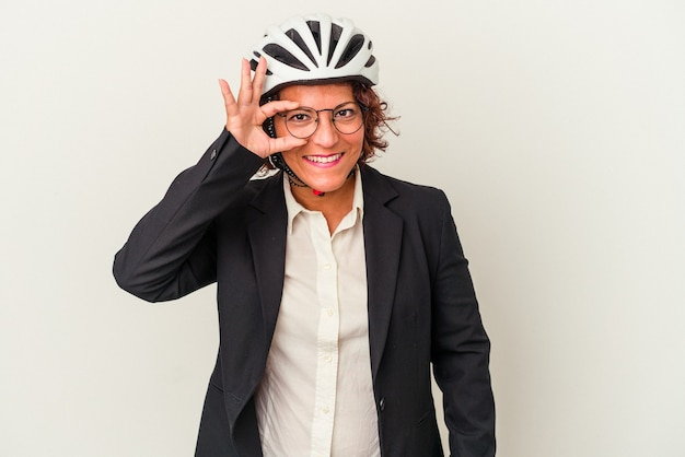 Middle age latin business woman wearing a bike helmet isolated on white background excited keeping ok gesture on eye.