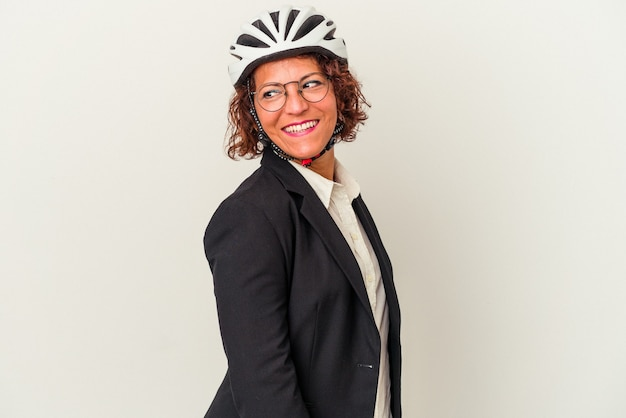 Middle age latin business woman wearing a bike helmet isolated on white background looks aside smiling, cheerful and pleasant.