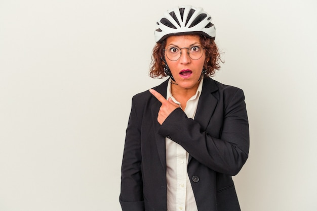 Middle age latin business woman wearing a bike helmet isolated on white background pointing to the side