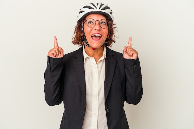 Middle age latin business woman wearing a bike helmet isolated on white background pointing upside with opened mouth.