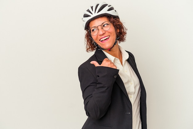 Middle age latin business woman wearing a bike helmet isolated on white background points with thumb finger away, laughing and carefree.