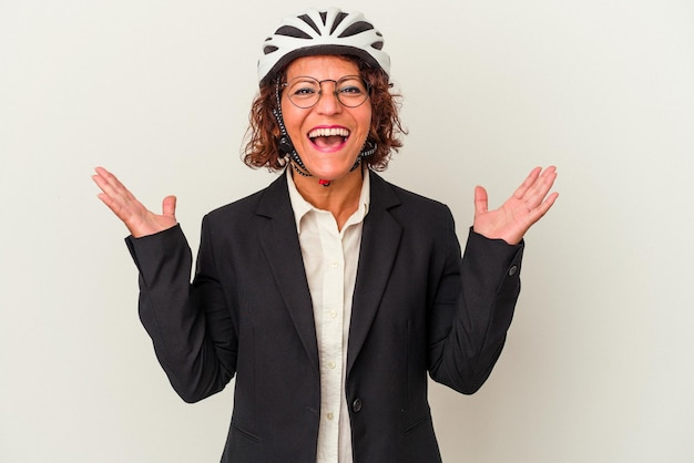 Middle age latin business woman wearing a bike helmet isolated on white background receiving a pleasant surprise, excited and raising hands.
