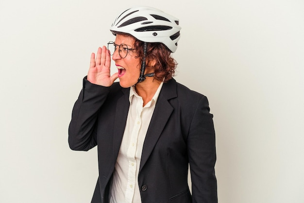 Middle age latin business woman wearing a bike helmet isolated on white background shouting and holding palm near opened mouth.