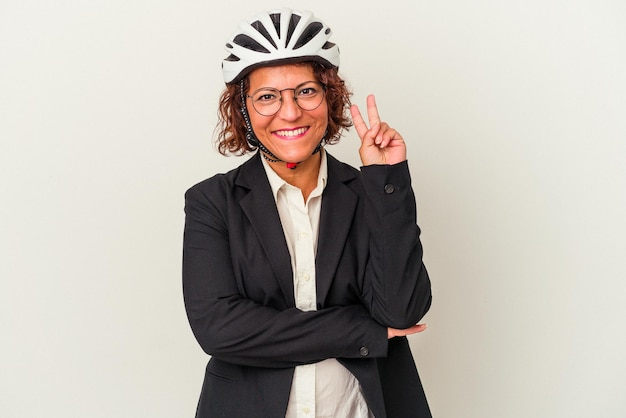 Middle age latin business woman wearing a bike helmet isolated on white background showing number two with fingers.