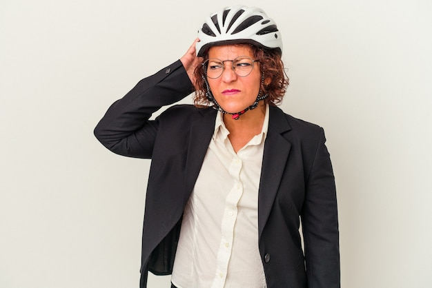 Middle age latin business woman wearing a bike helmet isolated on white background touching back of head, thinking and making a choice.
