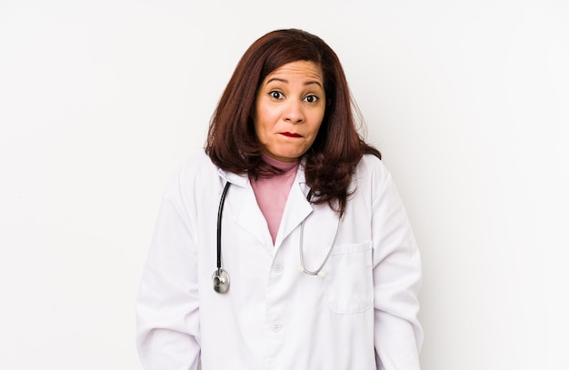 Middle age latin doctor woman isolated shrugs shoulders and open eyes confused.