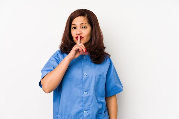 Среднего возраста латинская медсестра изолировала женщину, сохраняя тайну или прося молчания.