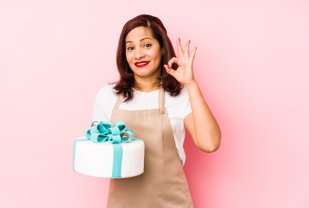 ピンクの背景に分離されたケーキを持っている中年のラテン女性は、陽気で自信を持って大丈夫なジェスチャーを示しています。