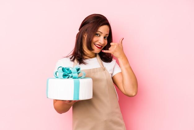 손가락으로 휴대 전화 제스처를 보여주는 분홍색 배경에 고립 된 케이크를 들고 중 년 라틴 여자.