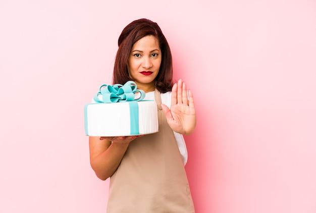 ピンクの背景に分離されたケーキを持っている中年のラテン女性は、一時停止の標識を示している手を伸ばして立って、あなたを防ぎます。