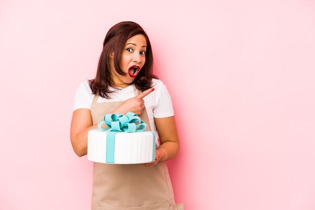 側面を指すピンクで隔離のケーキを保持している中年ラテン女性