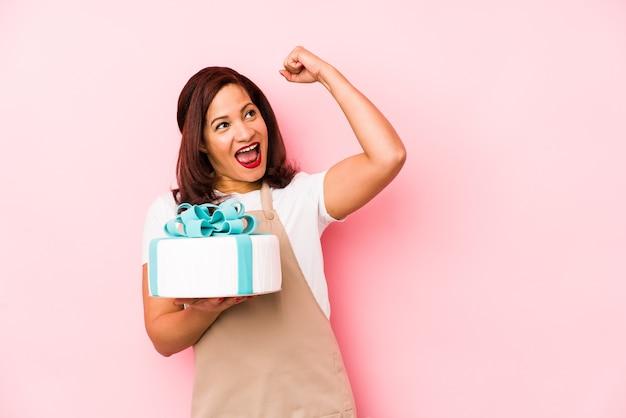 勝利、勝者のコンセプトの後にピンクのくいしばられた握りこぶしで隔離のケーキを保持している中年ラテン女性。