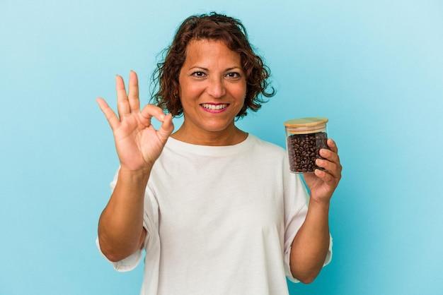 青の背景に分離されたコーヒー瓶を持っている中年のラテン女性は、陽気で自信を持って大丈夫なジェスチャーを示しています。