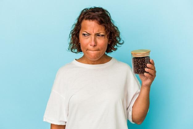 青い背景で隔離のコーヒー瓶を保持している中年のラテン女性は混乱し、疑わしく、不安を感じています。
