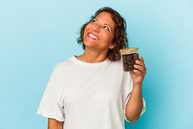 目標と目的を達成することを夢見て青い背景で隔離のコーヒー瓶を保持している中年ラテン女性