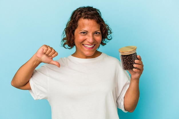 青い背景で隔離のコーヒー瓶を保持している中年のラテン女性は、誇りと自信を持って感じます、従うべき例。