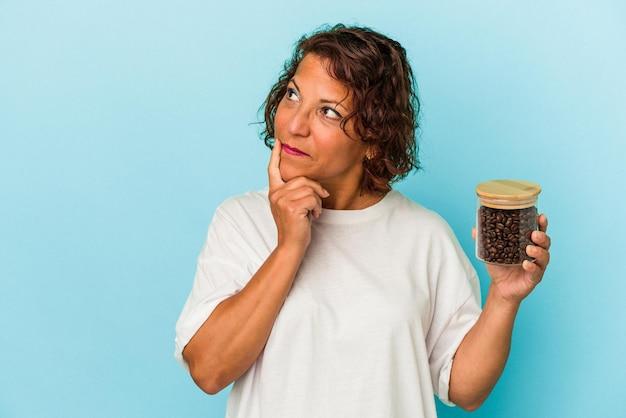 疑わしいと懐疑的な表情で横向きに青い背景で隔離のコーヒー瓶を保持している中年ラテン女性。