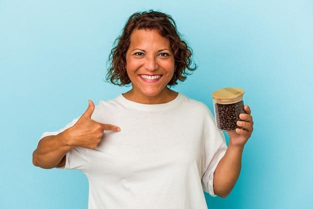 誇りと自信を持って、シャツのコピースペースを手で指している青い背景の人に分離されたコーヒー瓶を保持している中年ラテン女性