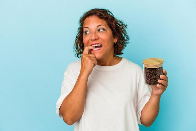 青い背景で隔離のコーヒー瓶を保持している中年ラテン女性は、コピースペースを見ている何かについて考えてリラックスしました。