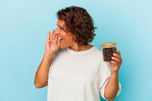 開いた口の近くで叫び、手のひらを保持している青い背景で隔離のコーヒー瓶を保持している中年ラテン女性。