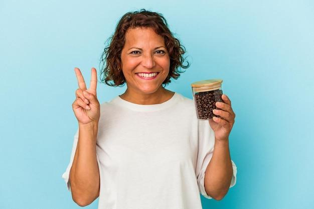 指で2番目を示す青い背景で隔離のコーヒー瓶を保持している中年ラテン女性。