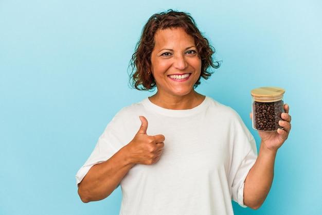 笑顔と親指を上げる青い背景で隔離のコーヒー瓶を保持している中年ラテン女性
