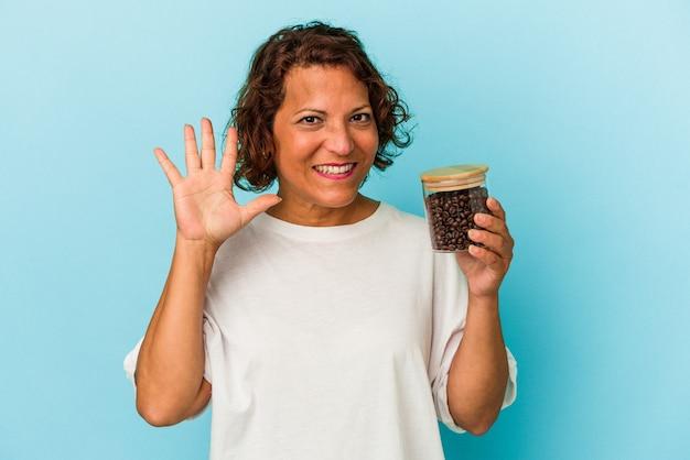 青い背景に分離されたコーヒー瓶を持っている中年のラテン女性は、指で5番を示して陽気に笑っています。