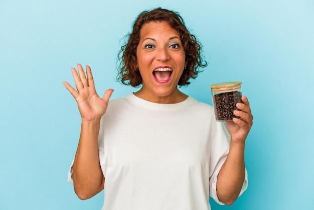青い背景で隔離のコーヒー瓶を保持している中年ラテン女性は驚いてショックを受けました。