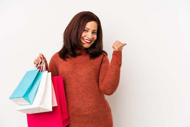 Латинская женщина среднего возраста, держащая сумку для покупок, изолирована, улыбаясь и поднимая палец вверх