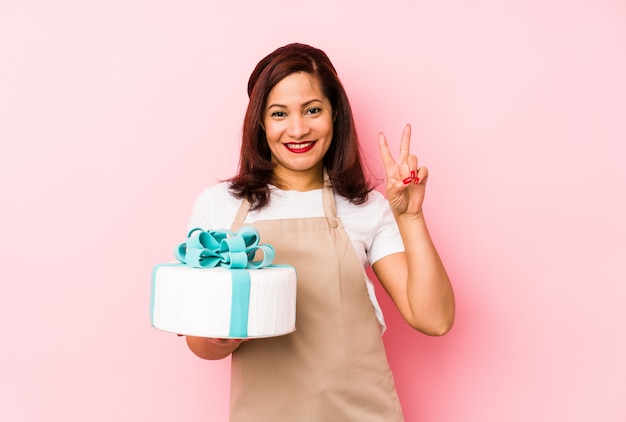 Middle age latin woman holding a cake isolated on pink showing number two with fingers.