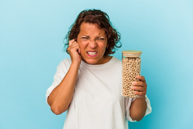 Middle age latin woman holding chickpeas jar isolated on blue background covering ears with hands.