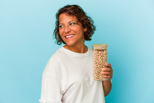 Middle age latin woman holding chickpeas jar isolated on blue background looks aside smiling, cheerful and pleasant.