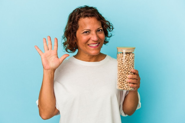 Middle age latin woman holding chickpeas jar isolated on blue background smiling cheerful showing number five with fingers.