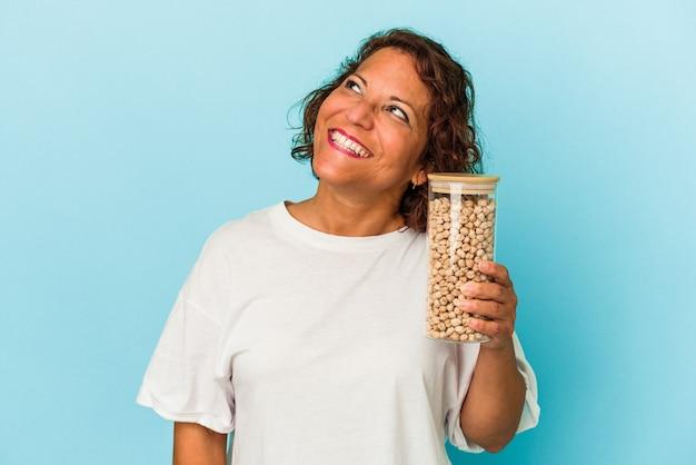 目標と目的を達成することを夢見て青い背景で隔離のひよこ豆の瓶を保持している中年ラテン女性 Premium写真