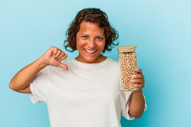 青い背景に分離されたひよこ豆の瓶を保持している中年のラテン女性は、誇りと自信を感じています。