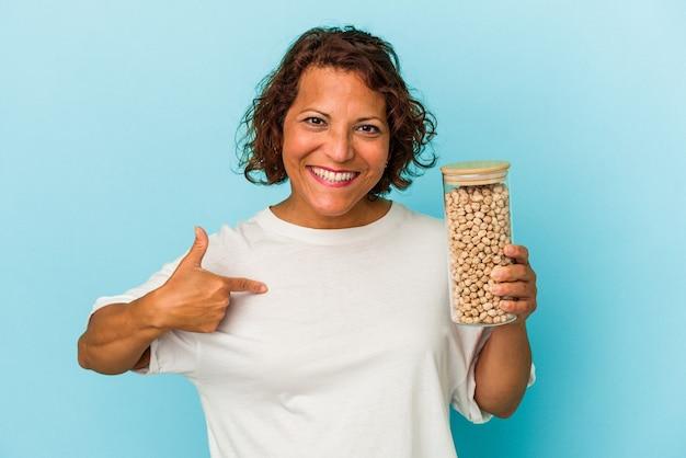 ひよこ豆の瓶を保持している中年のラテン女性は、シャツのコピースペースを手で指している青い背景の人に分離され、誇りと自信を持っています