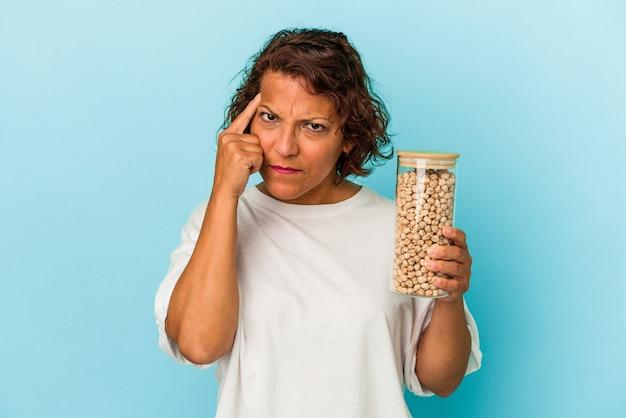 ひよこ豆の瓶を保持している中年のラテン女性は、指で寺院を指して、思考、タスクに焦点を当て、青い背景で隔離。