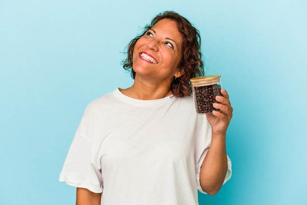Middle age latin woman holding a coffee jar isolated on blue background dreaming of achieving goals and purposes