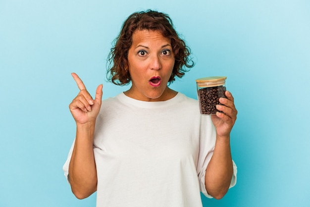 Middle age latin woman holding a coffee jar isolated on blue background having some great idea, concept of creativity.