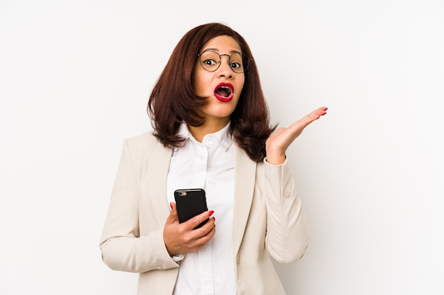 Middle age latin woman holding a mobile phone isolated surprised and shocked.