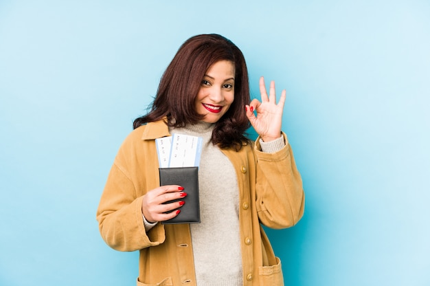 Middle age latin woman holding a passport isolated cheerful and confident showing ok gesture.