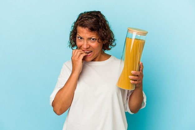Middle age latin woman holding pasta jar isolated on blue background biting fingernails, nervous and very anxious.