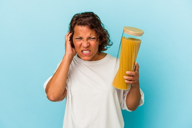 Middle age latin woman holding pasta jar isolated on blue background covering ears with hands.