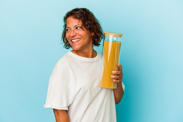 Middle age latin woman holding pasta jar isolated on blue background looks aside smiling, cheerful and pleasant.