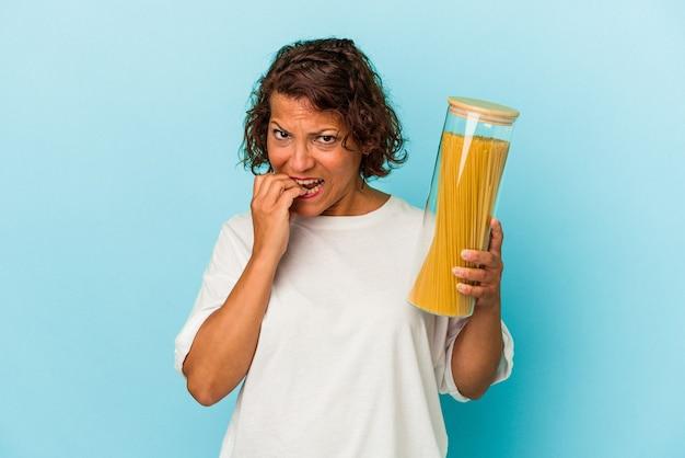 指の爪を噛んで、神経質で非常に心配している青い背景で隔離のパスタ瓶を保持している中年ラテン女性。