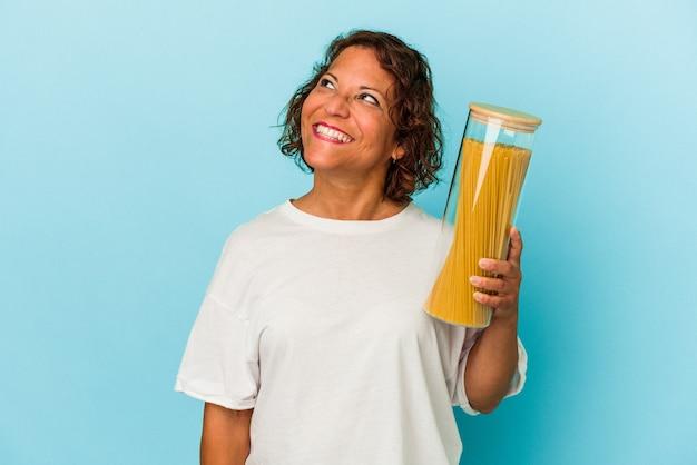 目標と目的を達成することを夢見て青い背景で隔離のパスタ瓶を保持している中年ラテン女性