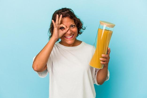 青い背景に分離されたパスタの瓶を保持している中年のラテン女性は、目に大丈夫なジェスチャーを維持して興奮しています。