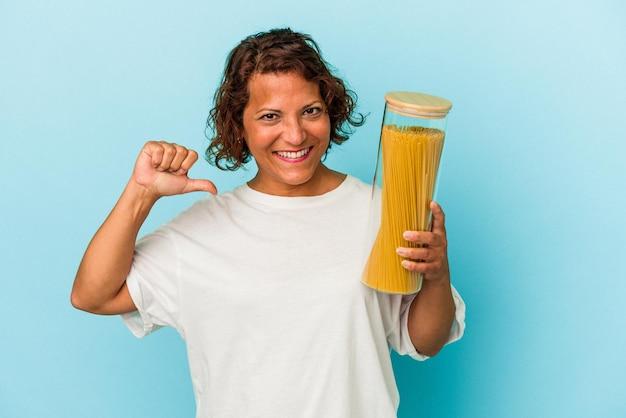 青い背景に分離されたパスタの瓶を保持している中年のラテン女性は、誇りと自信を感じています。 Premium写真
