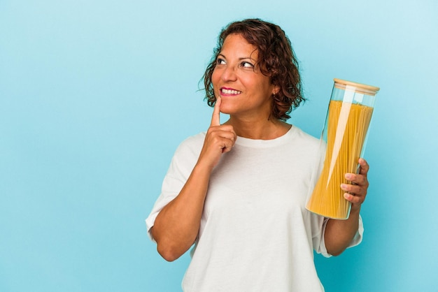 疑わしいと懐疑的な表情で横向きに青い背景で隔離のパスタ瓶を保持している中年ラテン女性。