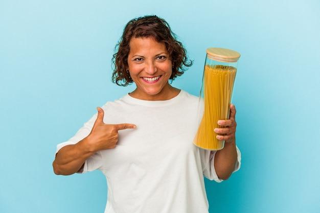 誇りと自信を持って、シャツのコピースペースを手で指している青い背景の人に分離されたパスタ瓶を保持している中年ラテン女性